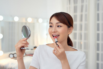 Beautiful young Asian girl applying lipstick while looking in the mirror