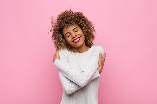 young african american woman feeling in love, smiling, cuddling and hugging self, staying single, being selfish and egocentric against pink wall