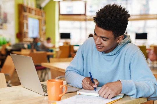 Smiling african bot teenager studying while sitting at the hub