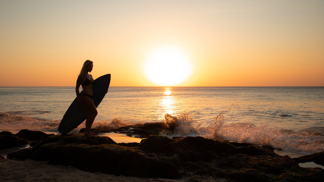 Surfing lifestyle. Surfer girl holding surfboard on the beach. Silhouette of surfer girl during sunset. Golden sunset time. Bali, Indonesia