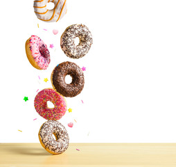 Flying donuts isolated on white. Mix of multicolored sweet doughnuts with sprinkel falling on the table
