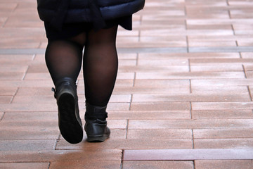 Fat woman walking down the street, thick legs in tights and black boots. Concept of overweight and diet