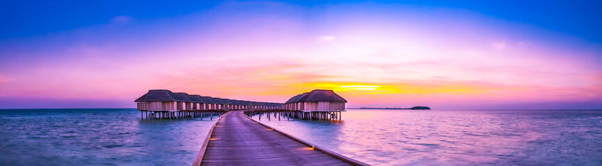 Türaufkleber Rosa hell Sunset on Maldives island, luxury water villas resort and wooden pier. Beautiful sky and clouds and beach background for summer vacation holiday and travel concept