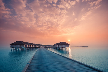 Wall Mural - Amazing sunset panorama at Maldives. Luxury resort villas seascape with soft led lights under colorful sky. Beautiful twilight sky and colorful clouds. Beautiful beach background for vacation holiday