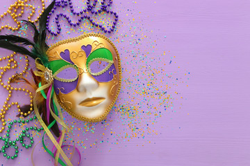 Holidays image of mardi gras masquarade, venetian mask and beads over purple background. view from above