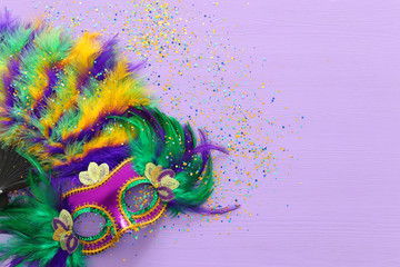Holidays image of mardi gras masquarade, venetian mask and fan over purple background. view from above Wall mural