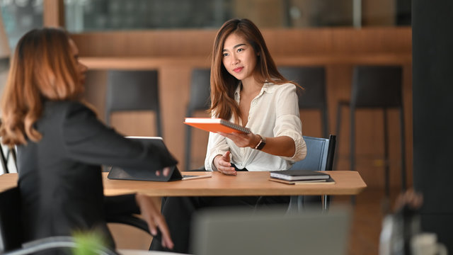 Young beautiful confident girl in white shirt giving a minutes of meeting to her colleague while sitting at wooden table in the modern office.