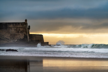Detail of the Sao Juliao da Barra Fort with its reflection on the beach sand and the waves breaking at Carcavelos, Oeiras, Portugal