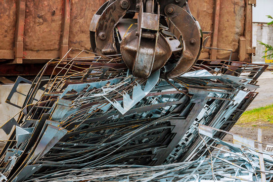 A grapple truck loads scrap industrial metal for recycling.