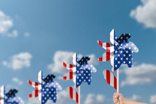 Hand holding wind turbine patriotic of USA over blue sky background.