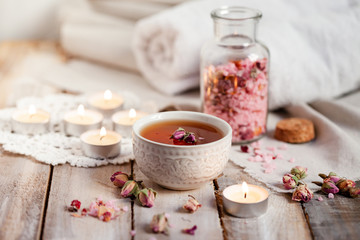 Foto op Aluminium Spa Concept of spa treatment with roses. Herbal tea, crystals of sea pink salt in bottle, candles as decor. Atmosphere of relax, anti-stress and detox procedure. Luxury lifestyle. Wooden background