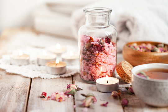 Concept of spa treatment with roses. Crystals of sea pink salt in bottle, candles as decor. Atmosphere of relax and pleasure. Anti-stress and detox procedure. Luxury lifestyle. Wooden background