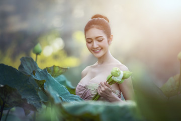 Asian woman harvest lotus flower in the garden, Thailand.
