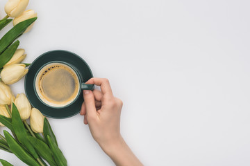 cropped view of woman holding cup of fresh coffee near tulips isolated on white
