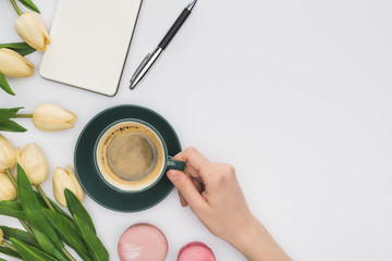 cropped view of woman holding coffee cup near tulips, blank notebook and delicious macarons isolated on white