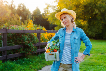 Young 30-35 years old beautiful Woman farmer in hat with box of fresh ecological vegetables on garden background at sunset.