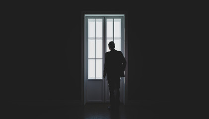 A man's silhouette in front of the window. Black and white. Concept of loneliness. 3d illustration
