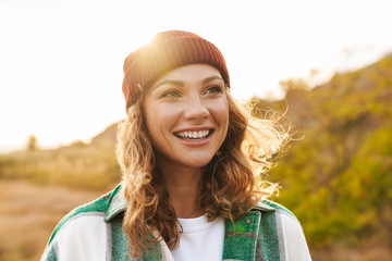 Image of young woman wearing hat and plaid shirt walking outdoors
