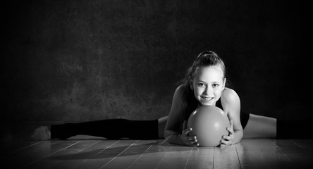 Young smiling girl gymnast in black sport body and uppers sitting in twine on floor and holding pink gymnastic ball in hands