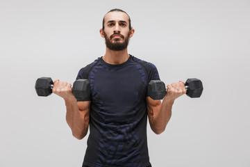 Image of young brunette sportsman wearing tracksuit lifting dumbbells