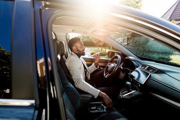 Young handsome African businessman using mobile phone, speaking through the loudspeaker, while sitting inside a luxury car