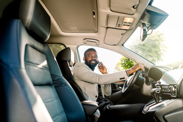 Young African American man in smart casual business wear, using phone sitting in the car, side view