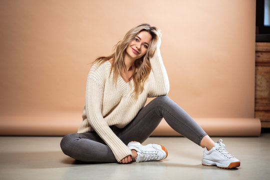 Beautiful blonde woman in a knitted sweater over brown background. Casual style, fashion beauty portrait