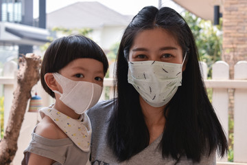 mother and kid wearing face mask protect air dust pollution with pm 2.5