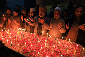 People pray and light candles for the victims, who were killed during heavy snowfall and avalanches in Neelum Valley, in Peshawar