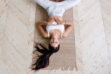 Top view pacified brunette woman in suit doing supta baddha konasana and meditating while lying on wooden floor in cozy relaxed home atmosphere. Concept of improvement of health. Advertising space