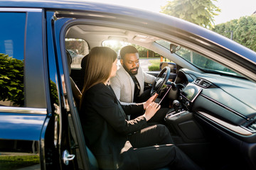 Young African American man communicating with female Caucasian coworker during car drive to business meeting discussing startup ideas and presentation from digital tablet