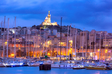 Fototapete - Panoramic view of Old Port and the Basilica of Notre Dame de la Garde on the background on the hill at sunset, Marseille, France
