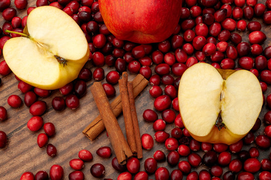 Christmas and holidays recipes, mulled wine ingredients and seasonal cooking concept with sliced red apples, heap of cranberries and cinnamon sticks isolated on wooden background