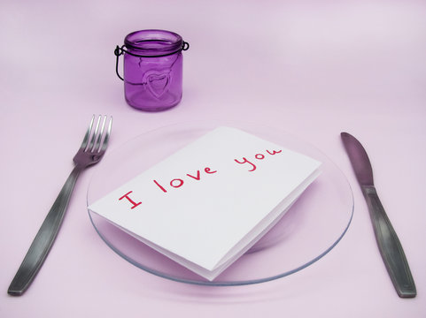 """A note with the text: """"I love you"""" on a transparent plate with Cutlery on a pink background.  In the background, a purple candlestick with a heart. The view from the top. Valentine's day."""