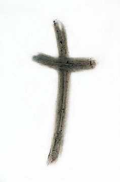 Ash cross isolated on wirte drawn with finger - Ash Wednesday, repentance and hope in Christ's atoning death concept.