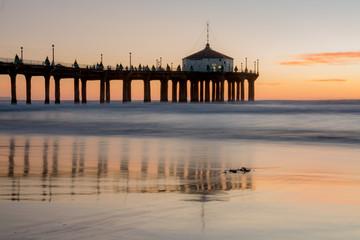 Views of the Manhattan Beach Pier and beach at sunset at Manhattan Beach in Los Angeles, California.