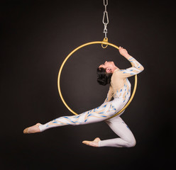 A slender,dark-haired girl - an air acrobat in a white and blue suit, performs exercises in an air ring.