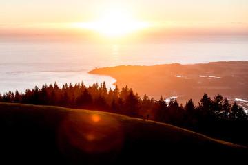A man on a hillside at sunset