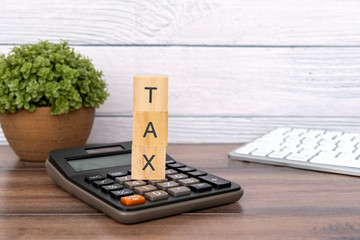 Tax text on a wood block and calculator on top of office desk - business and financial concept