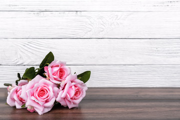 Pink roses on top of wooden table with copy space - Valentine's Day concept