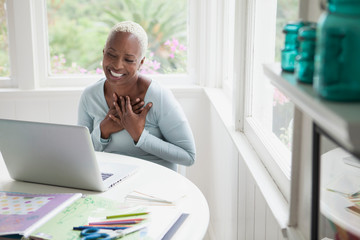 middle aged woman with hands over heart during online chat