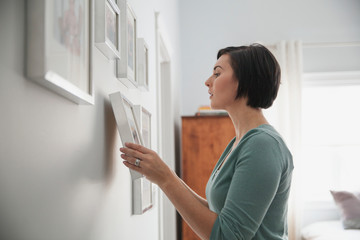 Side view of woman hanging picture frames