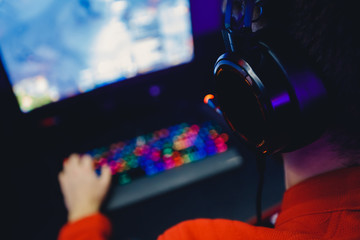 Professional gamer playing online games tournaments pc computer with headphones, Blurred red and...