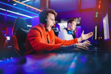 Streamer young man rejoices in victory professional gamer playing online games computer with headphones, neon color