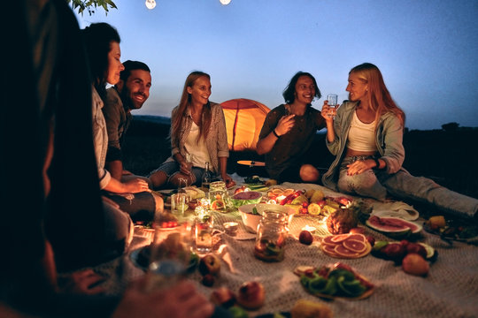 Happy friends having fun at bbq dinner with vintage lights outdoor drinking wine.