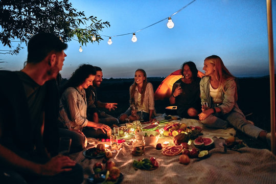 Group people rest near camping tent in evening time