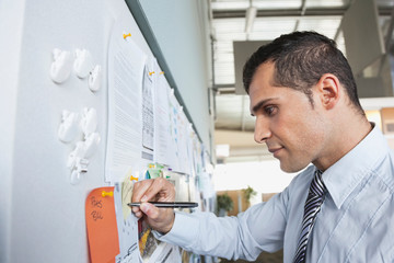 Businessman writing on notice board in office