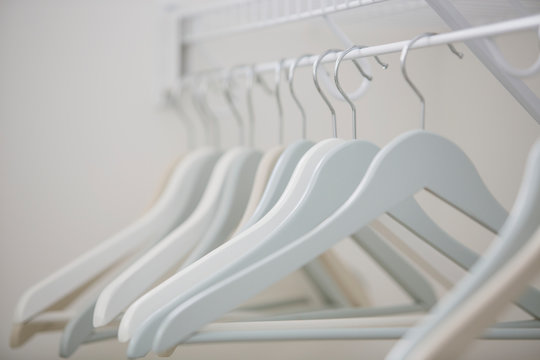 Close-up of white clothes hangers in closet.