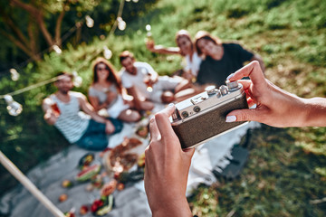 Woman taking picture of her friends by vintage camera on picnic at summer park