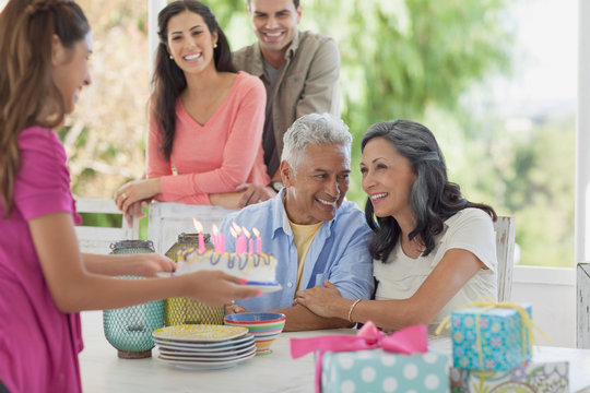 preteen daughter presenting birthday cake to parents